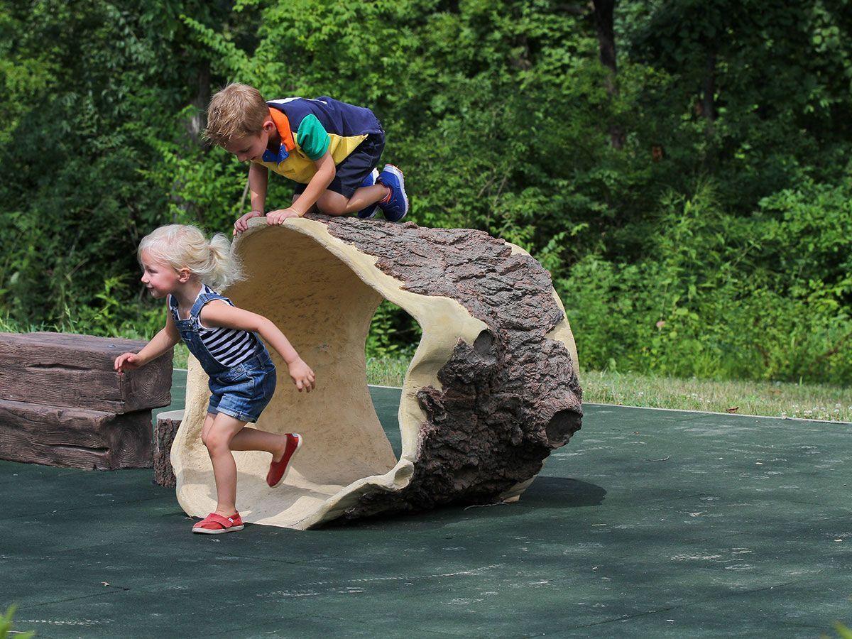 Young children running in playground tunnel