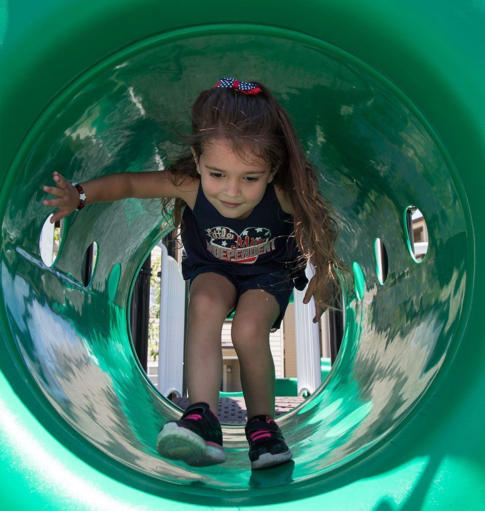 Girl at playground climbing in green tunnel