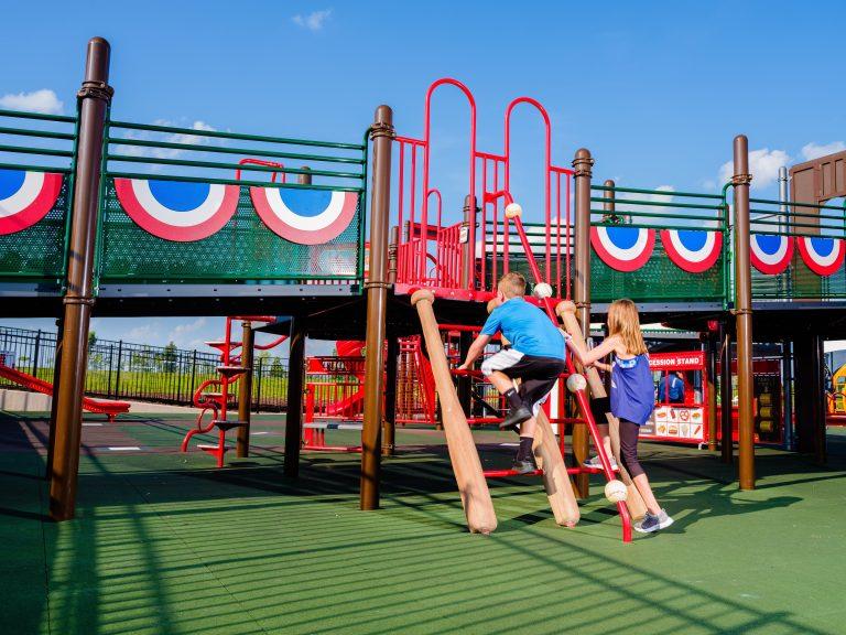Children climbing up baseball themed playground steps