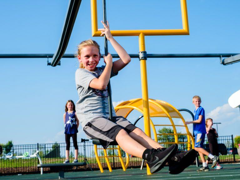Girl smiling on playground zipline