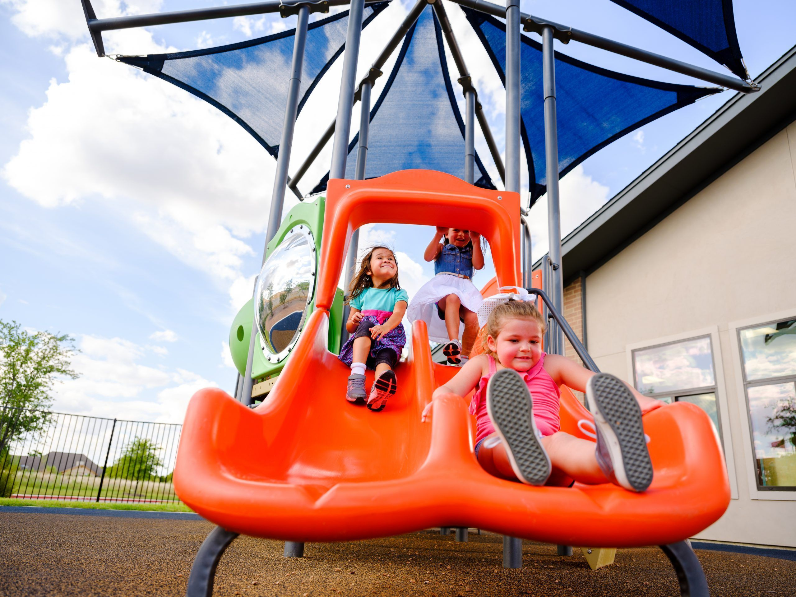 Girls sliding down Playbuilders structure