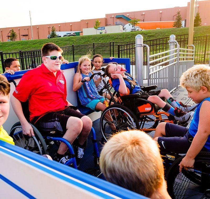 Children in wheelchairs on inclusive playground equipment