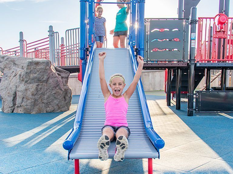Girl on commercial playground roller slide