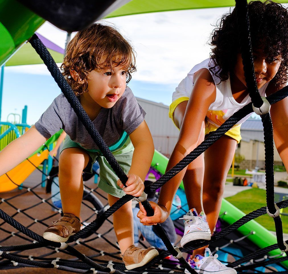 Young children with curly hair climbing on playground netting
