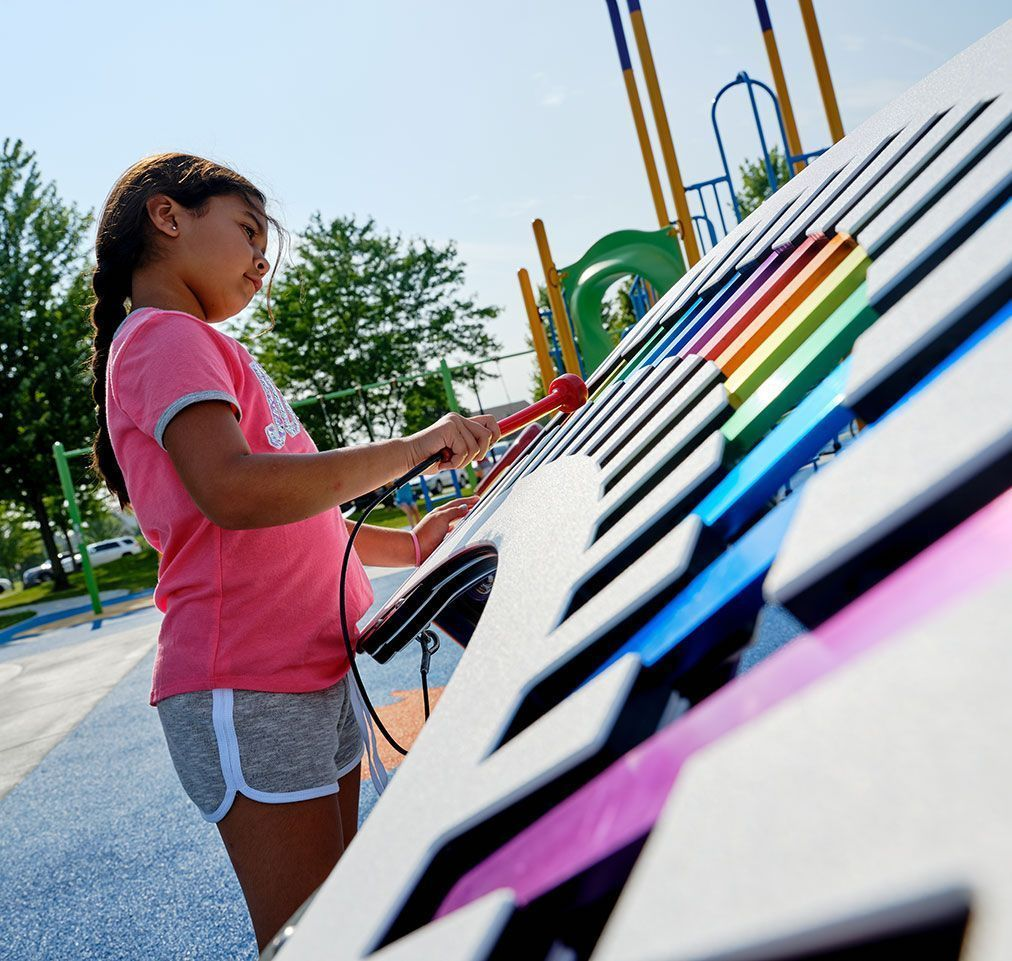 Young girl playing with vibes playground equipment