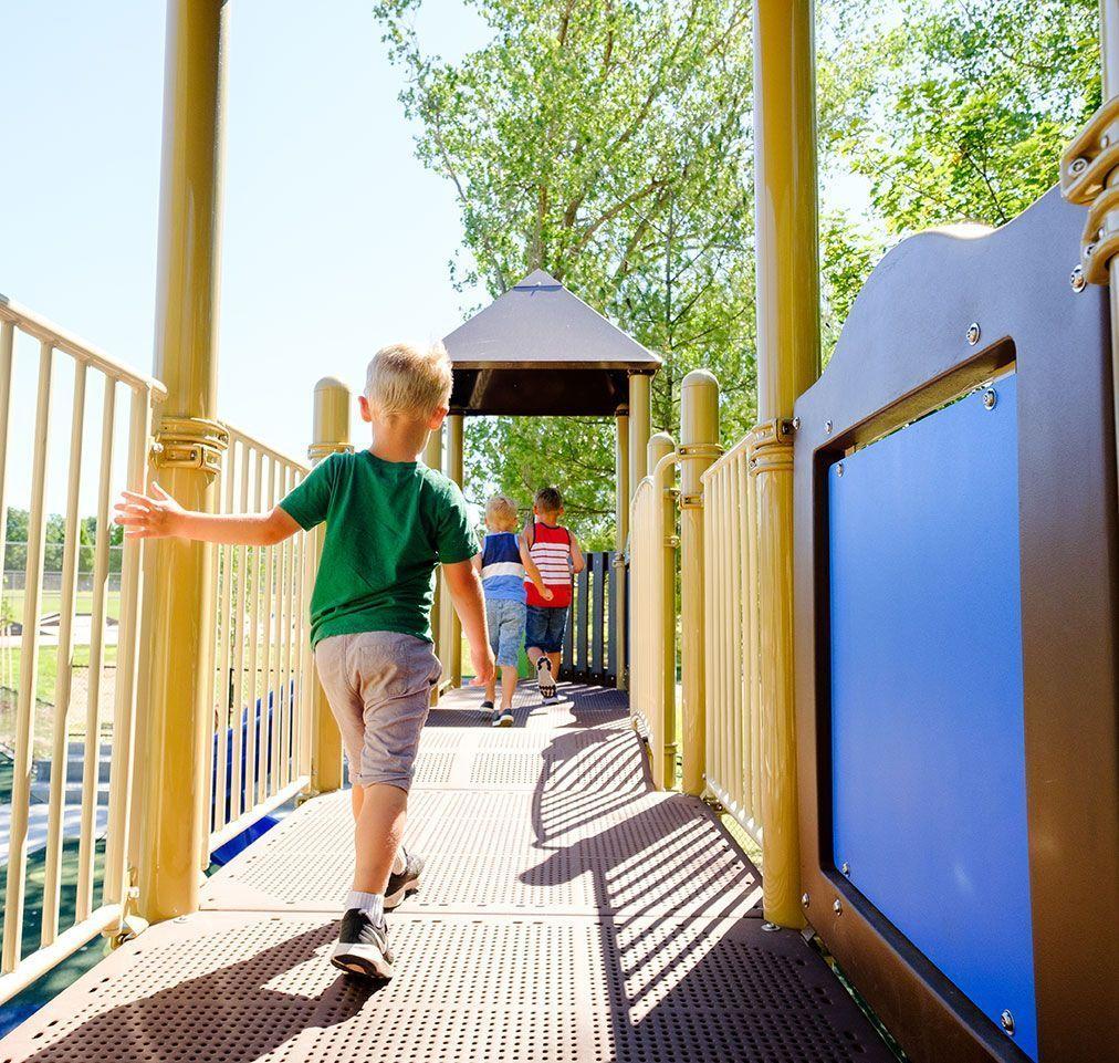 Young boy walking through playground equipment touching the railing