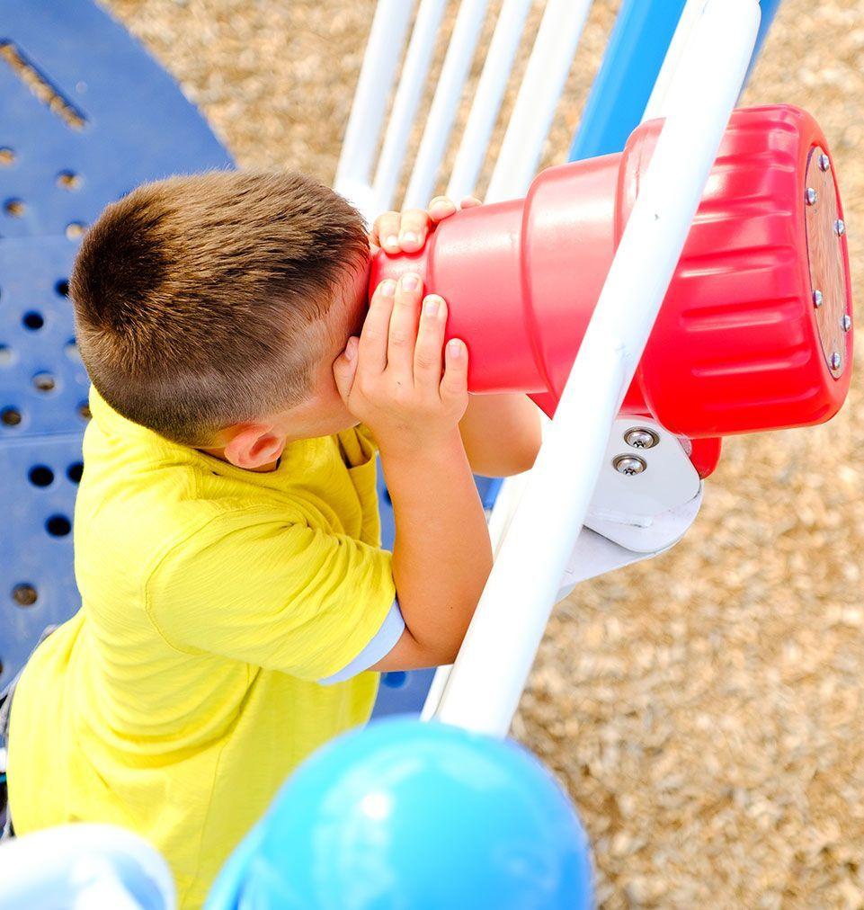 Boy looking through playground telescope