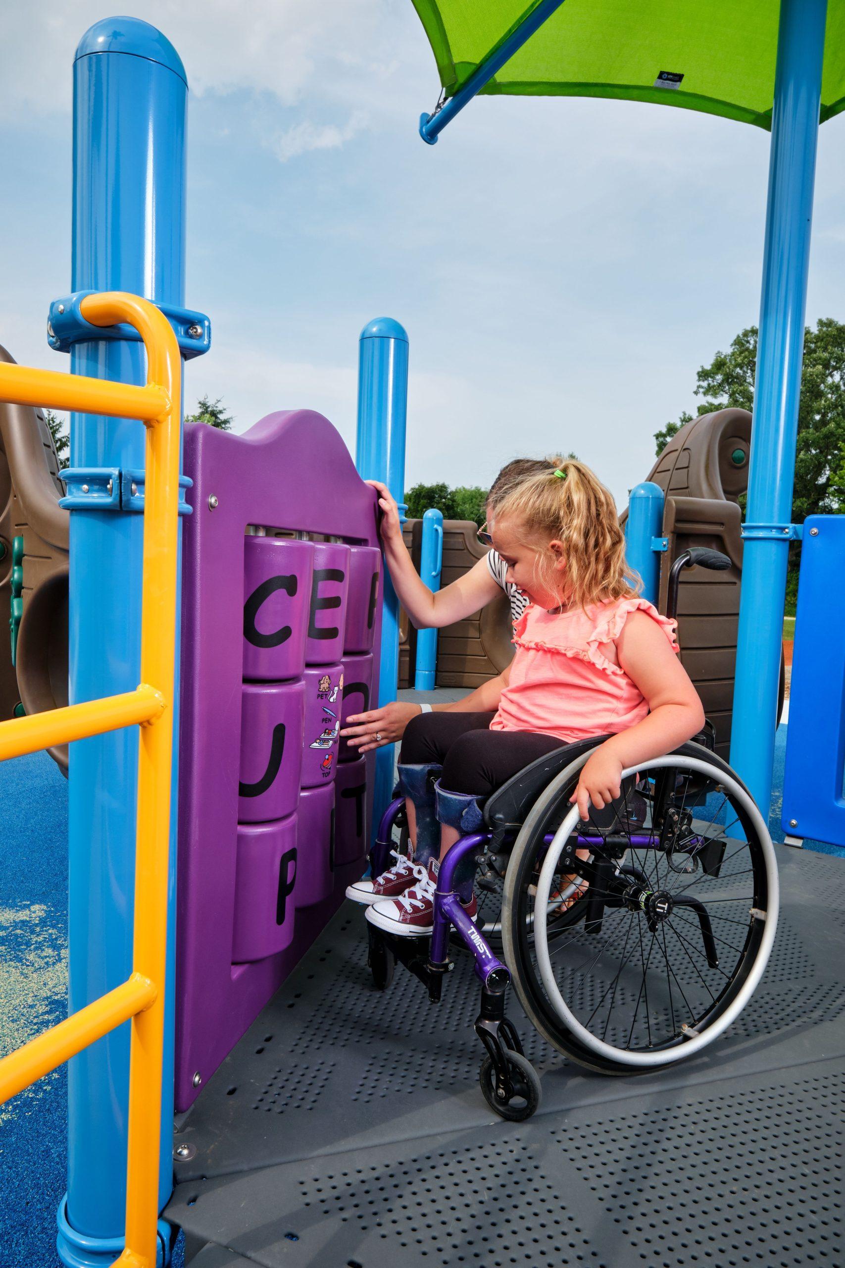 Girl in wheelchair using alphabet playground panel