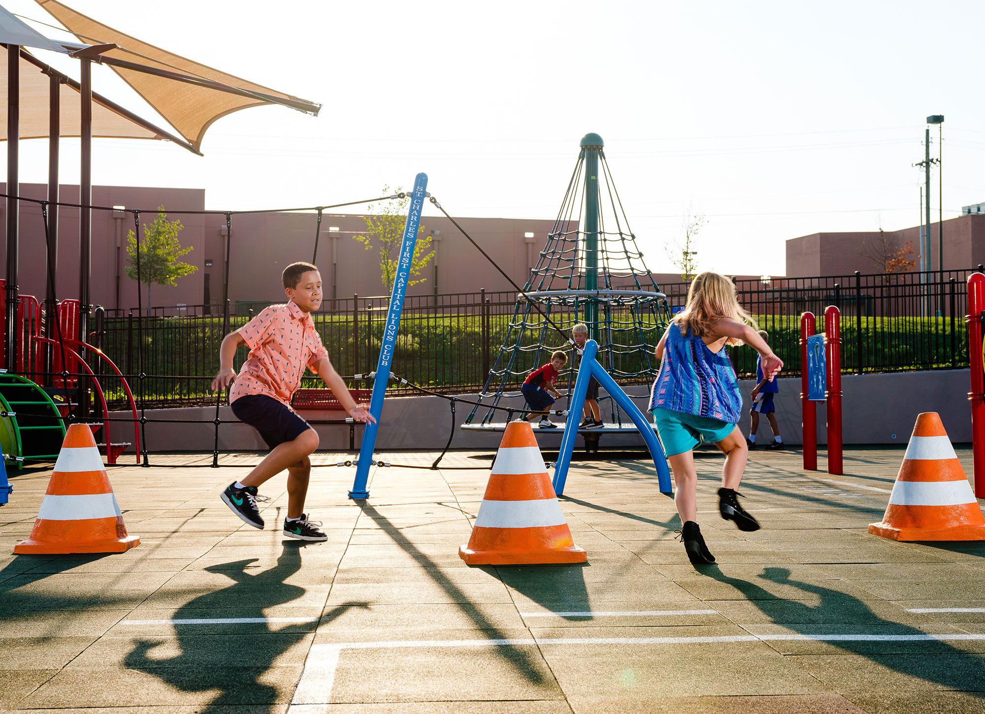 Children weaving through playground structure traffic cones