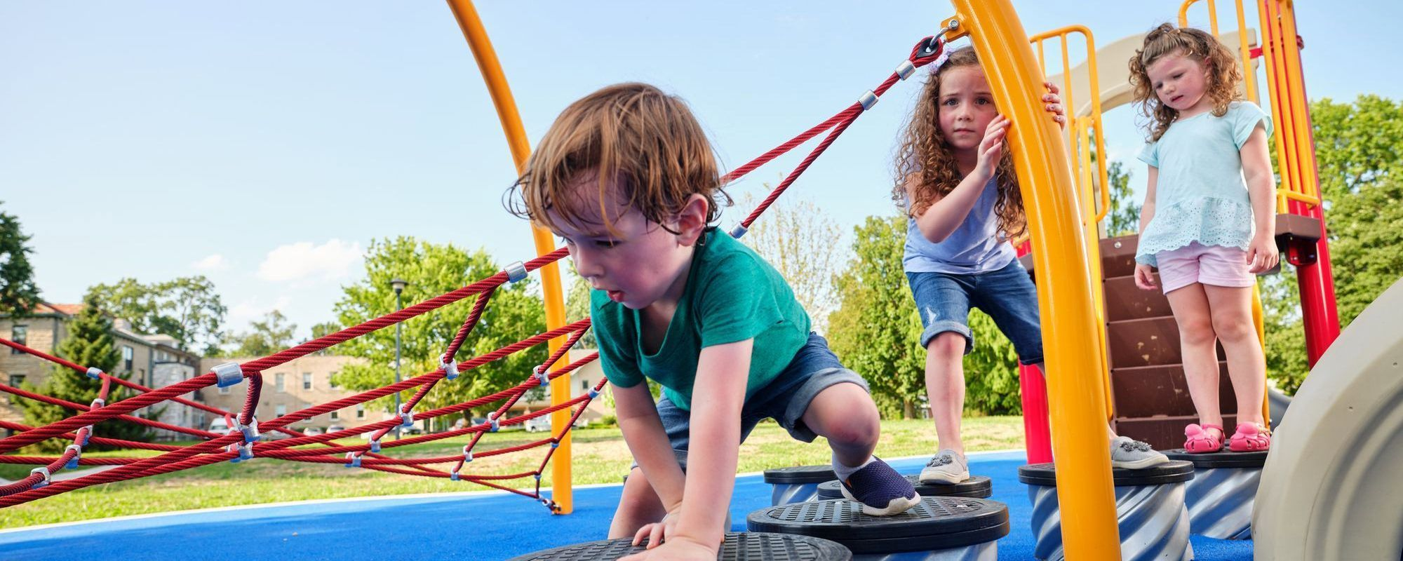 little boy crawling across playground steppers