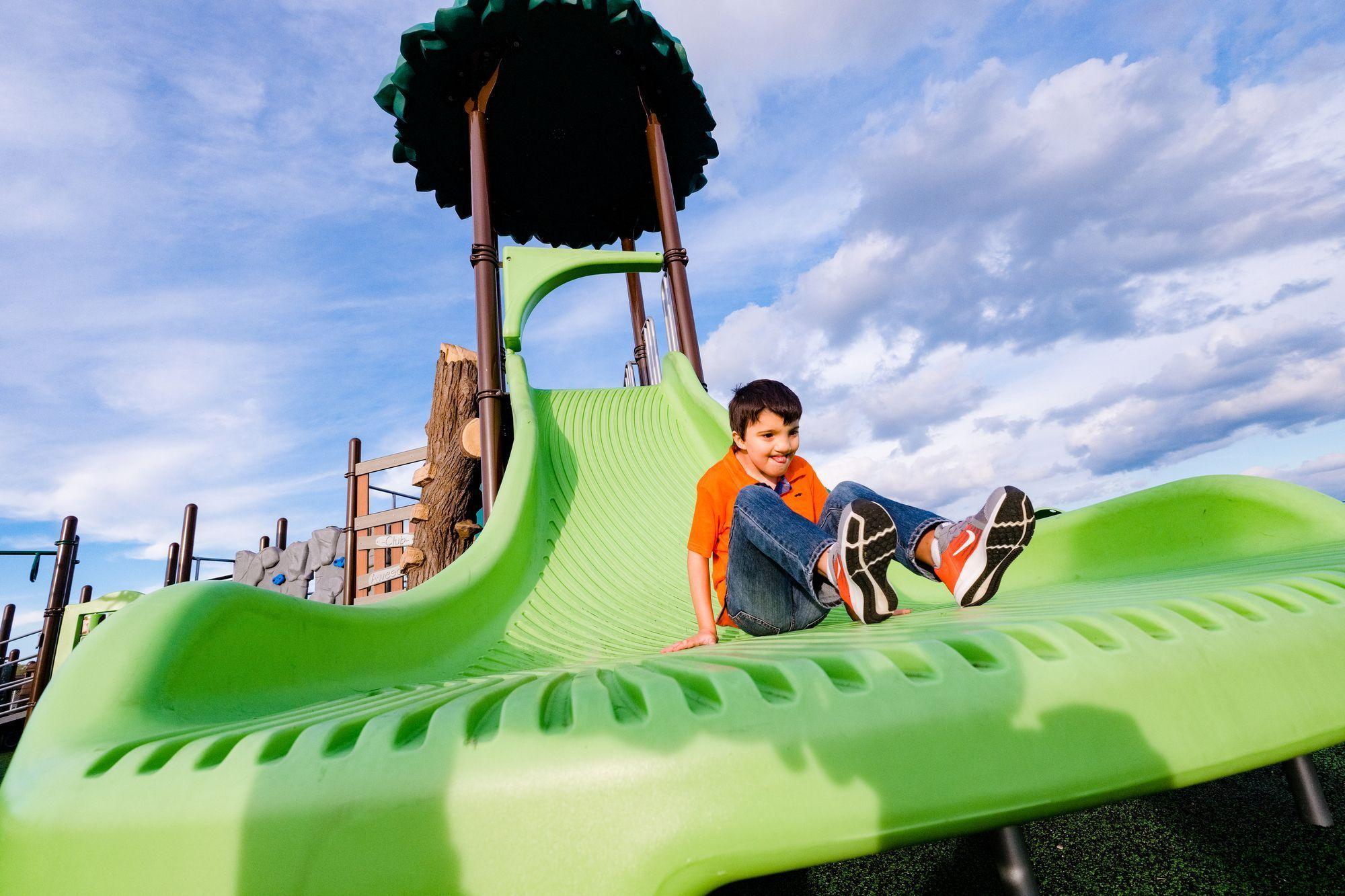 Boy on wide green playground slide