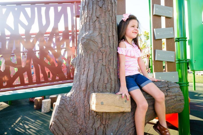 girl sitting on playground tree