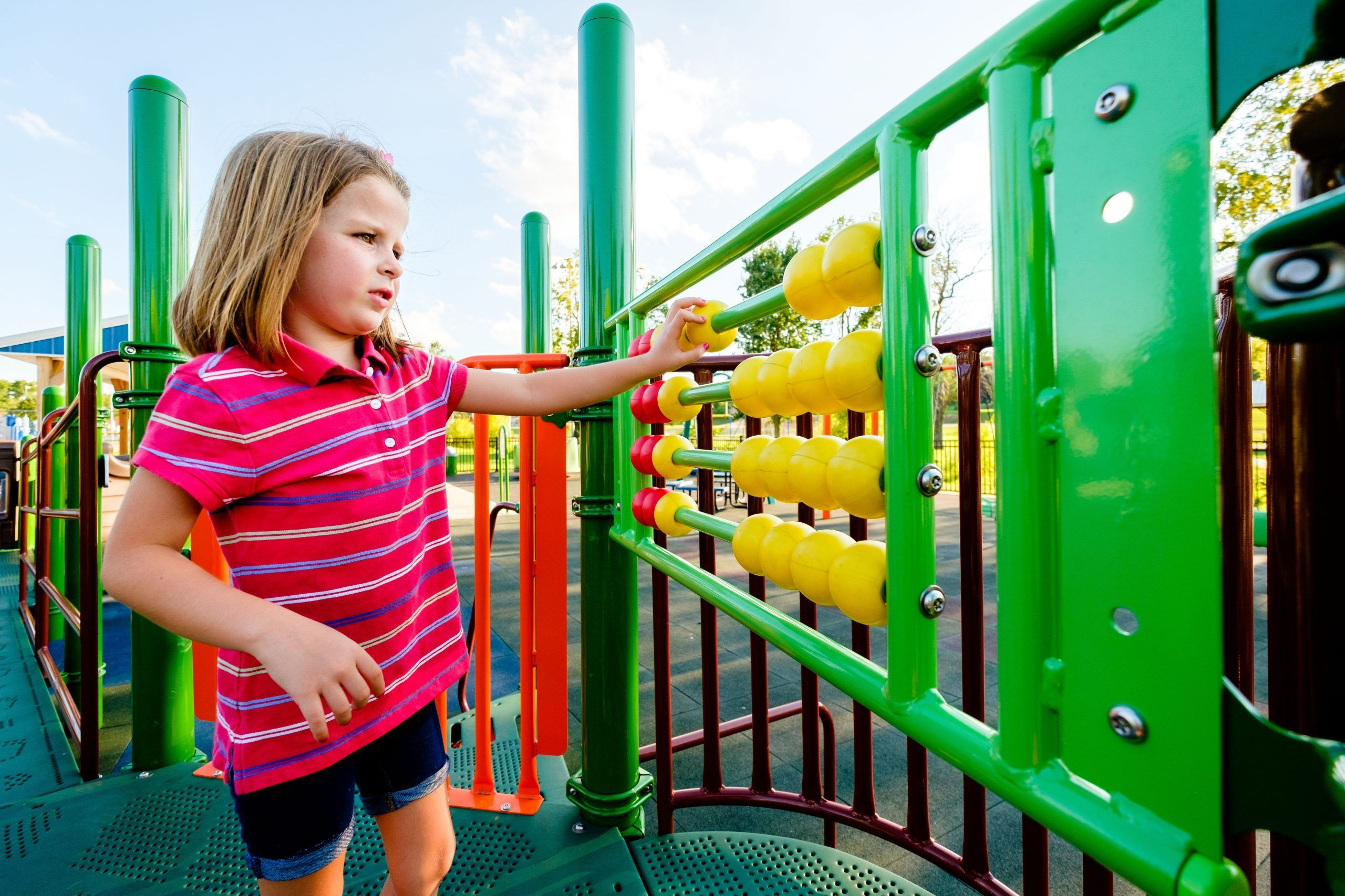 girl playing with playground beads