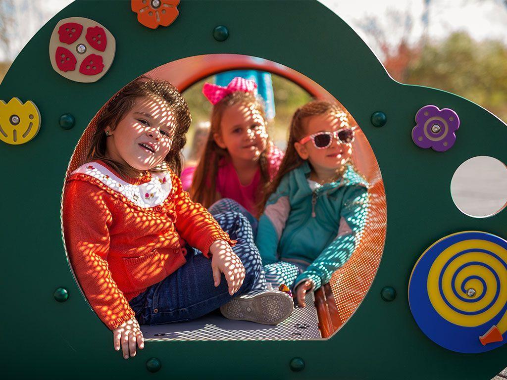 three girls sitting in playground tube