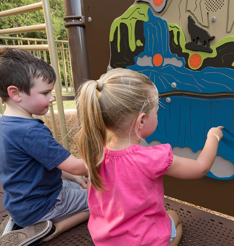 Children exploring sensory playground panels