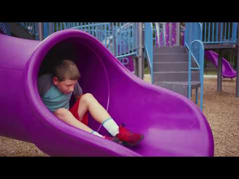 Boy sliding down purple tube slide