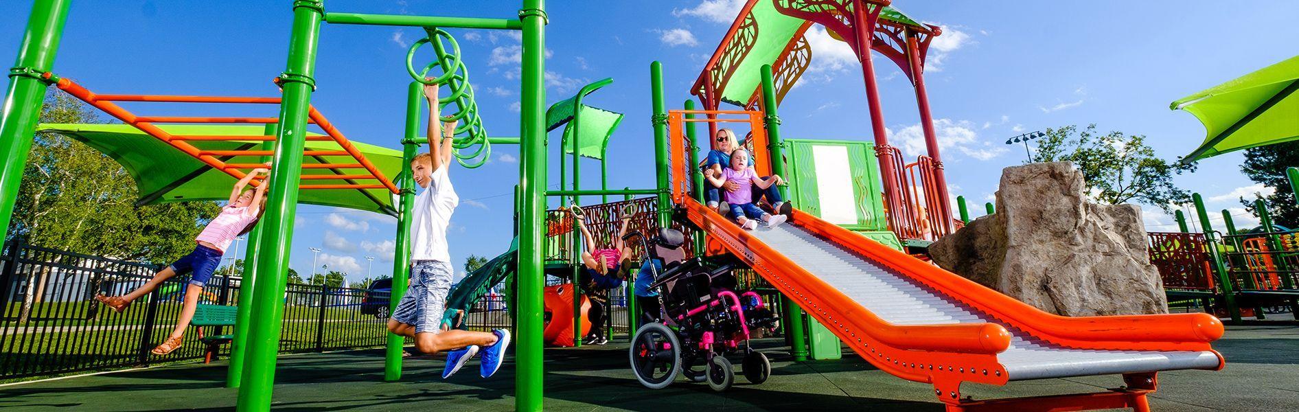 Child sliding down roller slide and kids hanging on monkey bars
