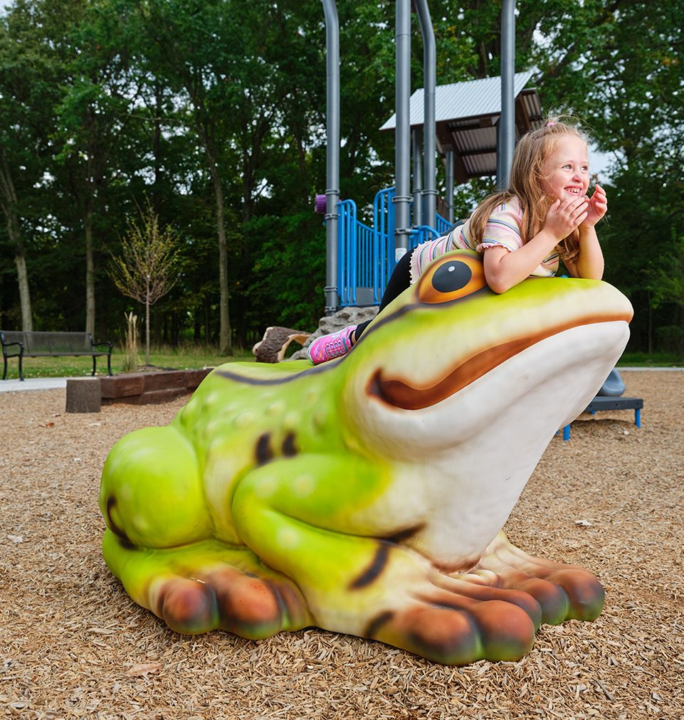 Girl playing on large frog playground sculpture