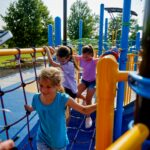 Girls playing on jungle gym in playground