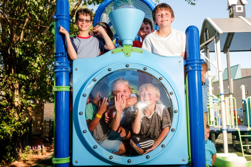children posing for picture on playground equipment