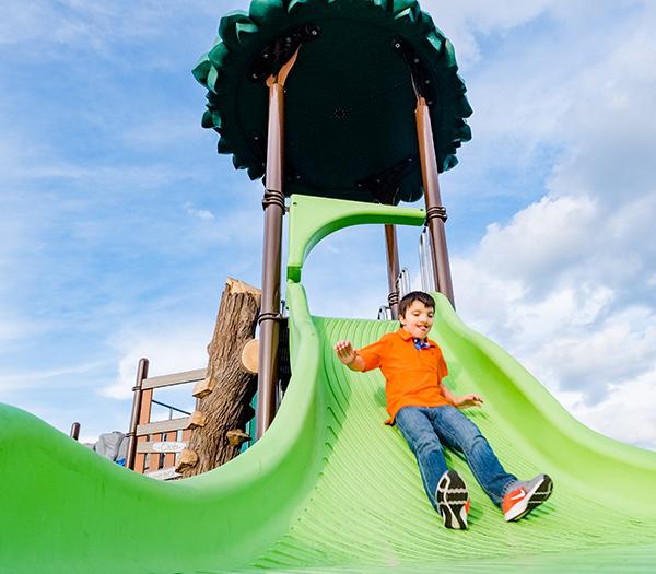 Young Boy sliding down green slide