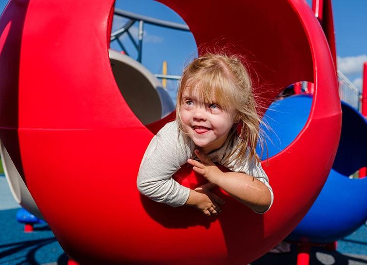 Girl peaking through red playground equipment