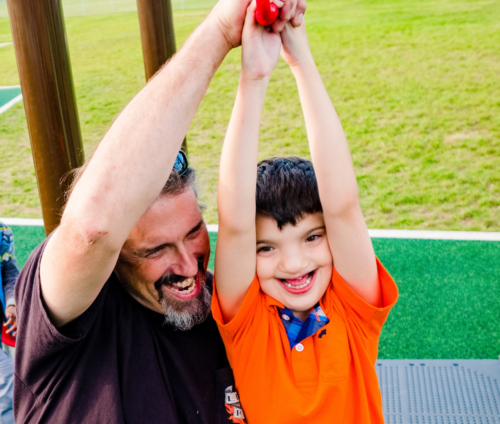Child and father smiling on playground zipline